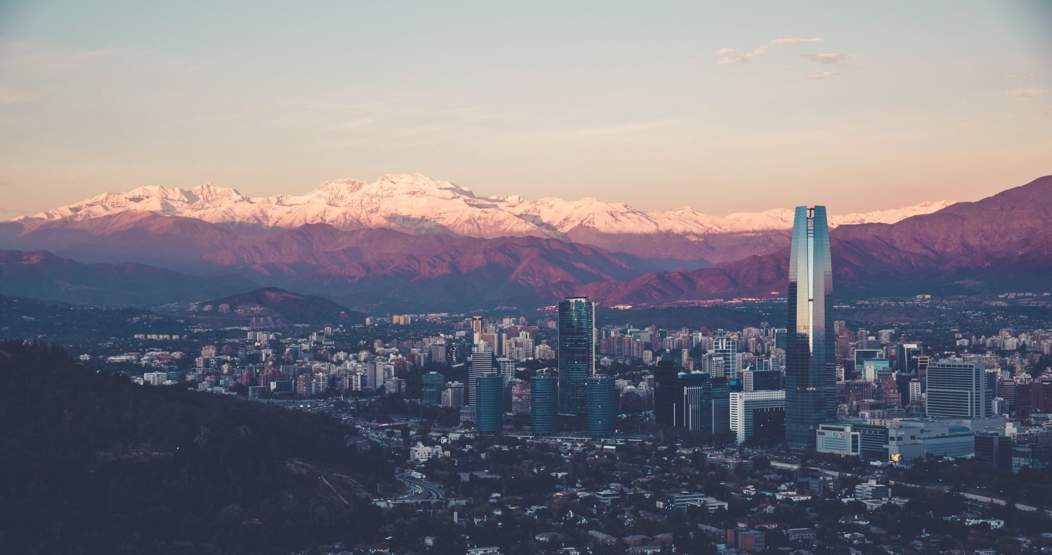 Photo of the Santiago city skyline in Chile with mountains in the background during sunset
